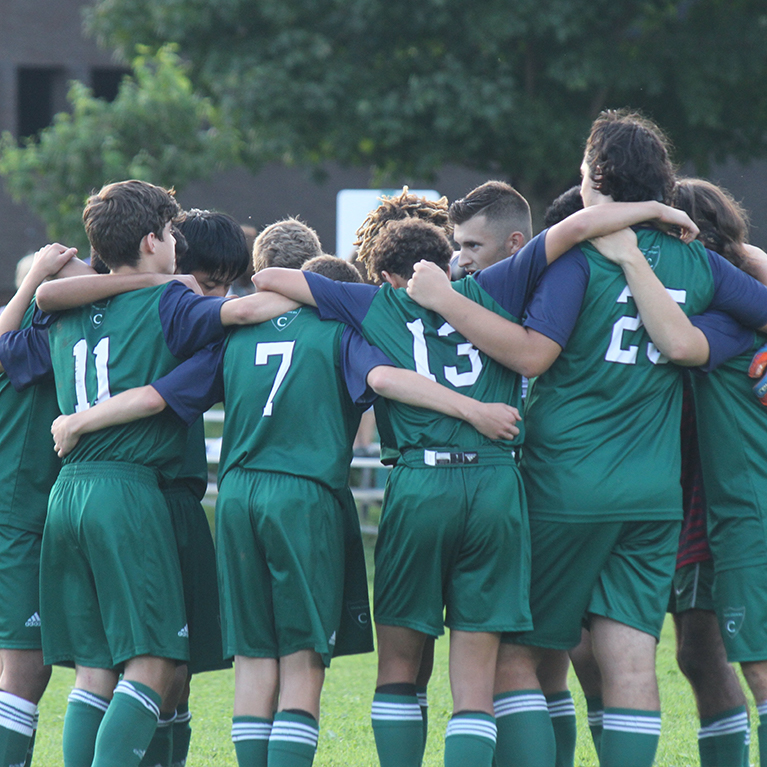 A Chase Collegiate athletics team huddles together before a game outside.