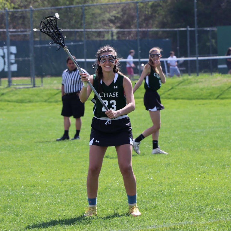 A Chase Collegiate girls' lacrosse player poses with her net on the Kelogg Fields.