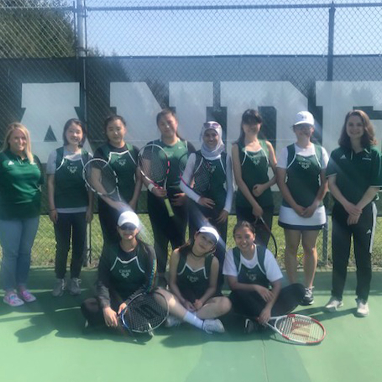 The Chase Collegiate girls' tennis team poses for a group photo on the court.