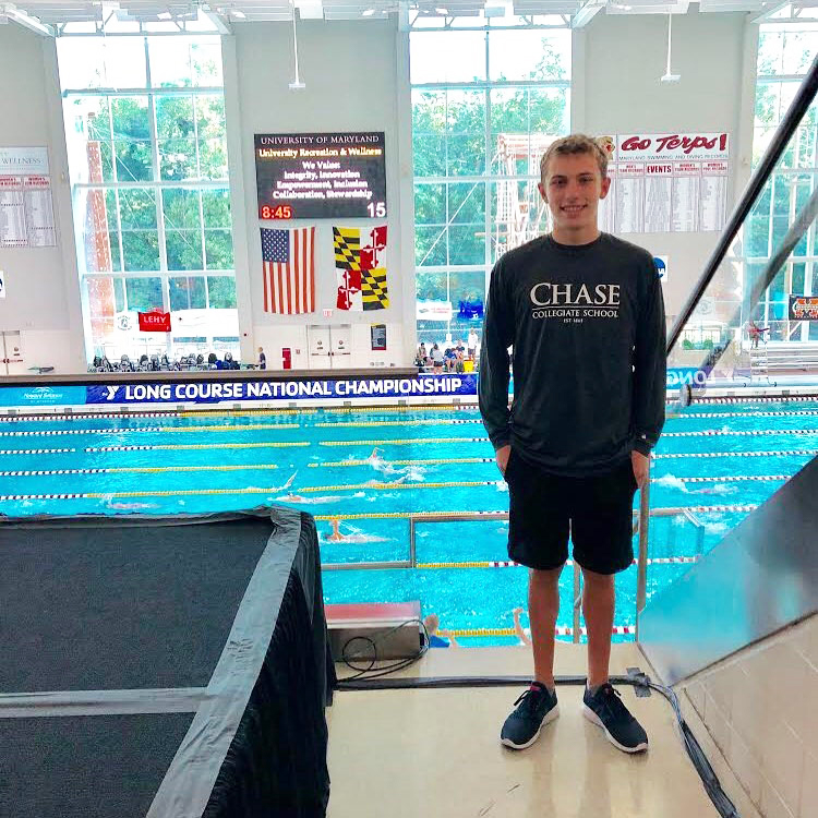 Chase Collegiate student Nate Stellmach stands in front of a swimming pull at the long course national championship.