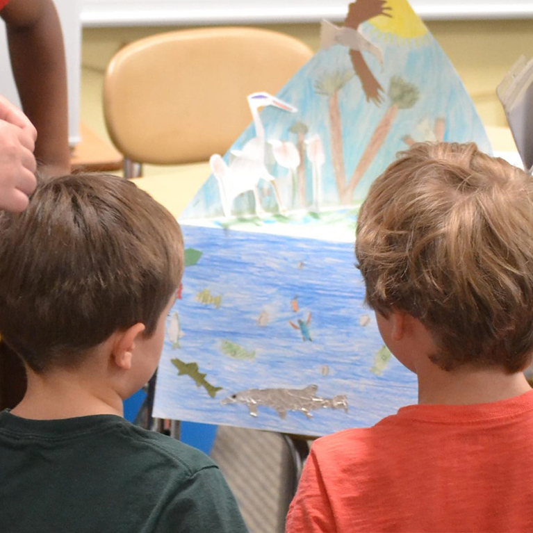 Lower School students look at their drawings at Chase Collegiate.