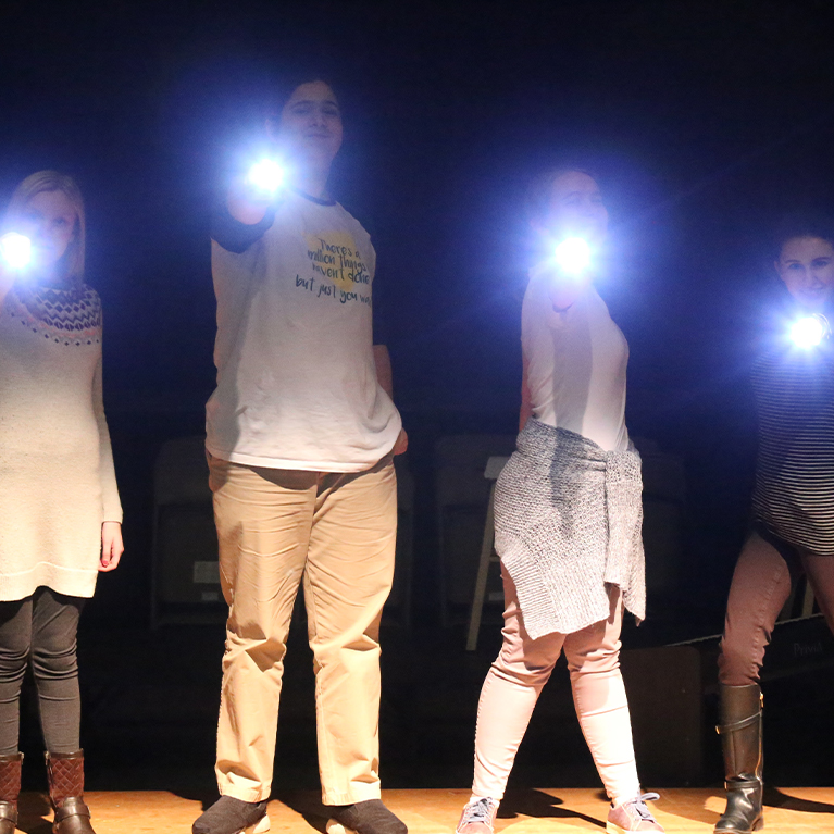 A group of young actors at Chase Collegiate pose with flashlights on stage during Theater rehearsal.