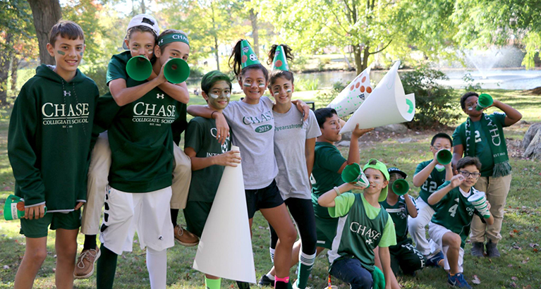 Chase Collegiate students pose together outside with megaphones and green accessories as they get into school spirit.