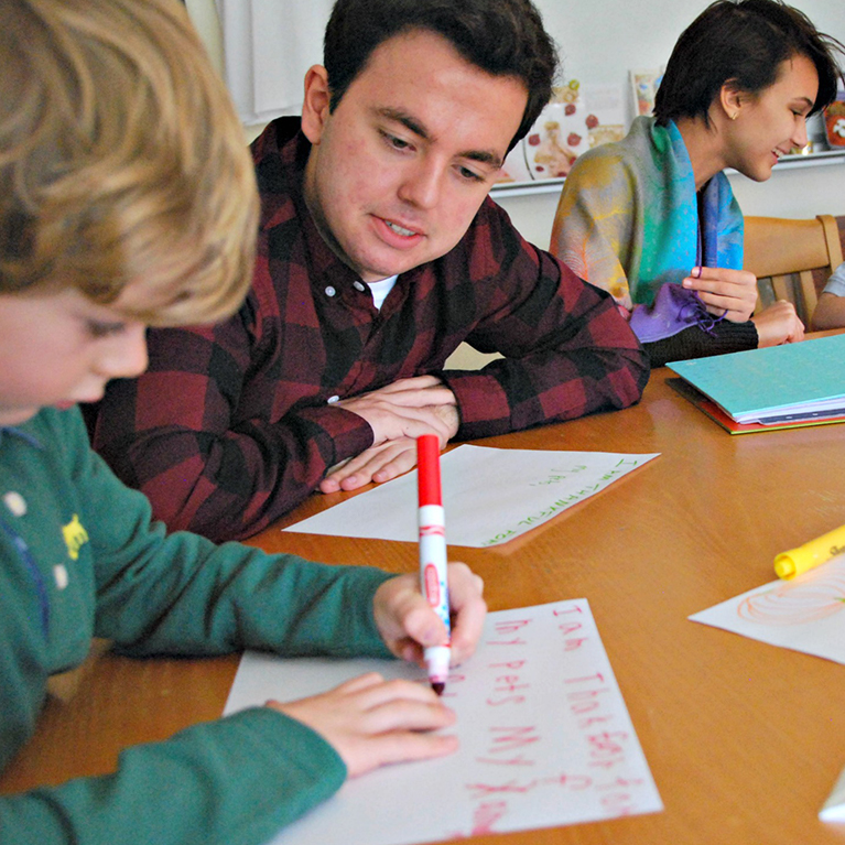 Upper School students at Chase Collegiate help younger students with writing.