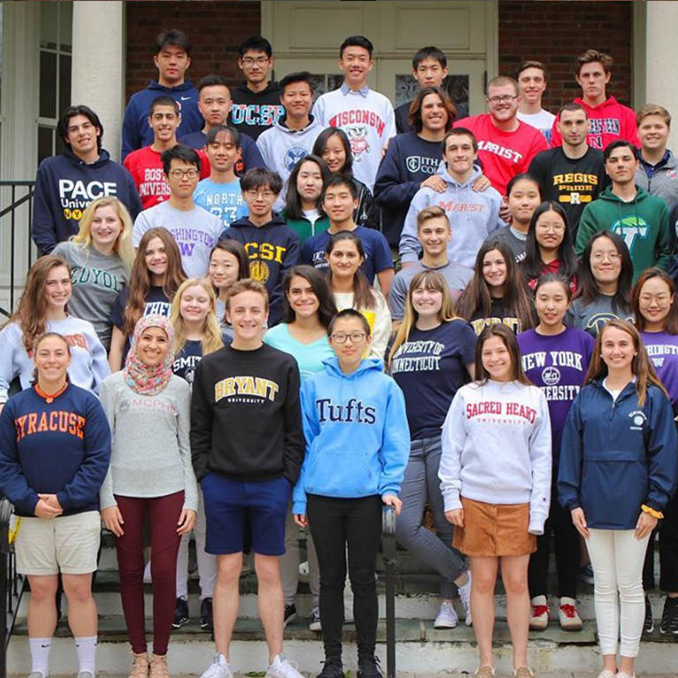 Chase Collegiate seniors pose outside in the shirts of the colleges they are going to in the Fall.