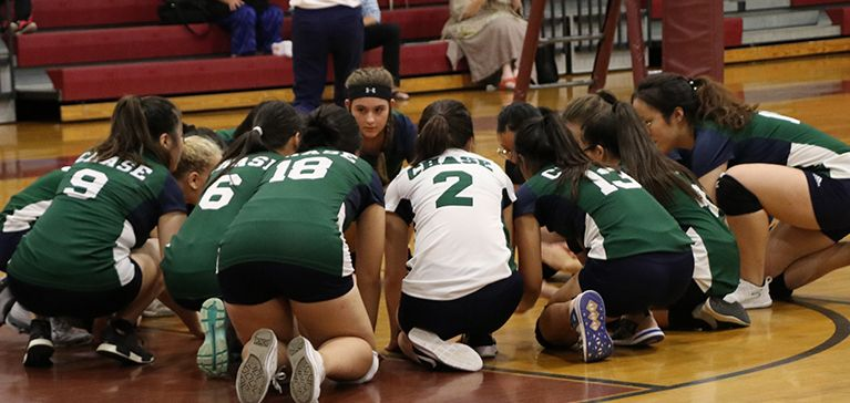 The Chase Collegiate Middle School girls' volleyball team huddles together before a match.