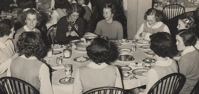 A group of girls sit around a table in a black and white photo of St. Margaret's School for Girls.