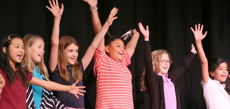 A group of girls at Chase Collegiate throw their hands up in the air laughing during Theater practice.
