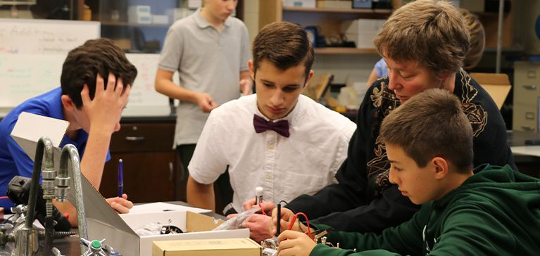 Chase Collegiate students work with electricity in Science class as their teacher helps them.