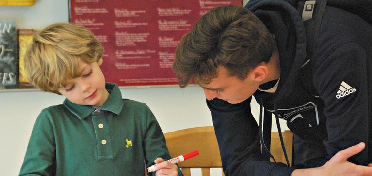 An Upper School Chase Collegiate student helps a Lower School student with his drawing.